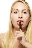 Schöne blonde Frau, die auf ihrer Schokolade Co leckt Stockfoto