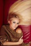Schöne blonde Frau, die auf rotem Sofa liegt Stockfotos