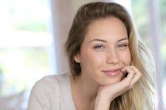 Schöne blonde Frau, die auf Sofa sich entspannt Lizenzfreies Stockfoto