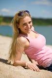 Schöne blonde Frau, die auf sonnigem Strand liegt Stockfotografie