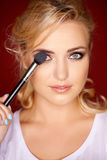 Schöne blonde Frau, die Augenmake-up anwendet Stockfotos