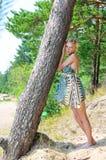 Schöne blonde Frau, die am Baum steht Lizenzfreie Stockfotos