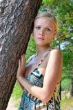 Schöne blonde Frau, die am Baum steht Stockfotografie
