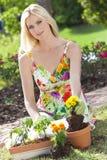 Schöne blonde Frau, die Blumen pflanzend im Garten arbeitet Stockfotografie