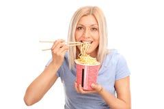 Schöne blonde Frau, die chinesische Nudeln isst Stockfoto
