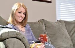Schöne blonde Frau, die Chips und Salsa isst Stockfotos