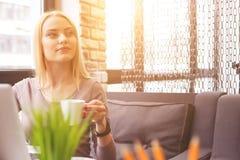 Schöne blonde Frau, die in der Cafeteria sich entspannt Lizenzfreies Stockbild
