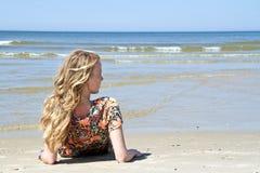 Schöne blonde Frau, die in der Ufergegend sich entspannt Stockfoto