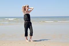 Schöne blonde Frau, die in der Ufergegend sich entspannt Lizenzfreie Stockfotografie