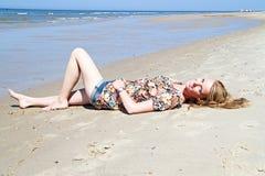 Schöne blonde Frau, die in der Ufergegend sich entspannt Lizenzfreie Stockbilder