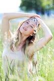 Schöne blonde Frau, die in der Wiese aufwirft Lizenzfreies Stockbild