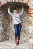 Schöne blonde Frau, die in der Ziegelsteinnische aufwirft Stockbilder