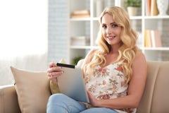 Schöne blonde Frau, die Digital-Tablet verwendet Lizenzfreies Stockfoto