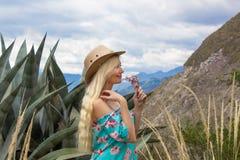 Schöne blonde Frau, die draußen den Hut im Grasland trägt Lizenzfreies Stockbild