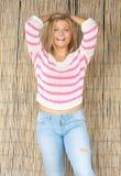 Schöne blonde Frau, die draußen mit den Händen im Haar lacht Lizenzfreie Stockbilder
