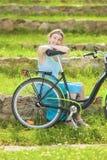 Schöne blonde Frau, die draußen Natur mit Fahrrad genießt Stockbild