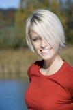Schöne blonde Frau, die durch einen See lächelt Lizenzfreie Stockfotografie