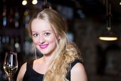 Schöne blonde Frau, die ein Glas Champagner oder prosecco genießt Lizenzfreie Stockfotografie