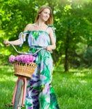 Schöne blonde Frau, die ein hübsches Kleid hat Spaß in Park wi trägt Lizenzfreie Stockfotografie