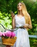 Schöne blonde Frau, die ein hübsches Kleid hat Spaß in Park wi trägt Stockbild