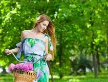 Schöne blonde Frau, die ein hübsches Kleid hat Spaß in Park wi trägt Stockfoto