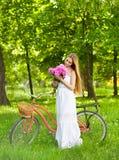 Schöne blonde Frau, die ein hübsches Kleid hat Spaß in Park wi trägt Stockfotos