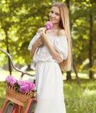 Schöne blonde Frau, die ein hübsches Kleid hat Spaß in Park wi trägt Lizenzfreie Stockfotos