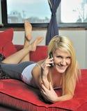 Schöne blonde Frau, die ein intelligentes Telefon verwendet Stockbild