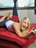 Schöne blonde Frau, die ein intelligentes Telefon verwendet Lizenzfreies Stockbild