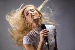 Schöne blonde Frau, die in ein Mikrofon singt Stockfotografie