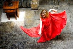 Schöne blonde Frau, die ein rotes Kleid trägt Stockfotos