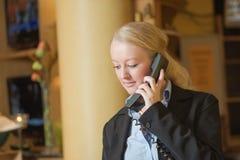 Schöne blonde Frau, die ein Telefon beantwortet Lizenzfreie Stockfotos