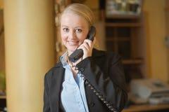 Schöne blonde Frau, die ein Telefon beantwortet Stockfotografie
