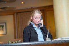 Schöne blonde Frau, die ein Telefon beantwortet Stockbild