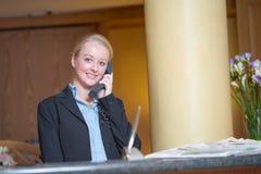 Schöne blonde Frau, die ein Telefon beantwortet Stockfotos