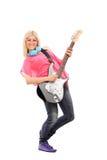 Schöne blonde Frau, die eine E-Gitarre spielt Stockbild