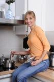 Schöne blonde Frau, die eine geschmackvolle Mahlzeit kocht Stockfotos