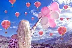 Schöne blonde Frau, die eine schöne Landschaft und Berge steht und betrachtet Und er hält rosa Bälle in seiner Hand lizenzfreie stockfotos