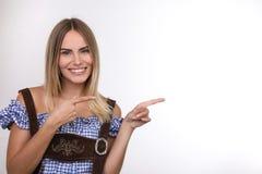Schöne blonde Frau, die in eine Richtung lächelt und zeigt Stockfotos