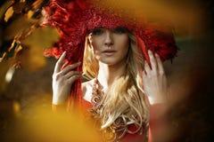 Schöne blonde Frau, die eine rote Krone trägt stockfotos