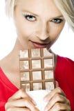 Schöne blonde Frau, die eine Schokolade hält Stockfotografie