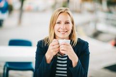 Schöne blonde Frau, die einen Bruch mit Tasse Kaffee hat Stockbilder