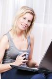 Schöne blonde Frau, die einen Computer verwendet. Lizenzfreies Stockbild