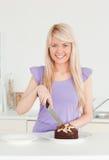 Schöne blonde Frau, die einen Kuchen in einer Platte schneidet Stockbild