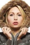 Schöne blonde Frau, die einen Parka mit Pelz trägt Stockfotografie