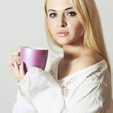 Schöne blonde Frau, die einen Tee trinkt Stockfoto