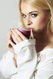 Schöne blonde Frau, die einen Tee trinkt. Dampf-Tasse Kaffee Stockfotografie