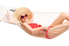 Schöne blonde Frau, die in einer Hängematte liegt Lizenzfreies Stockfoto