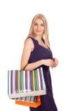 Schöne blonde Frau, die Einkaufstaschen anhält Lizenzfreie Stockbilder