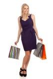 Schöne blonde Frau, die Einkaufstaschen anhält Stockfotos